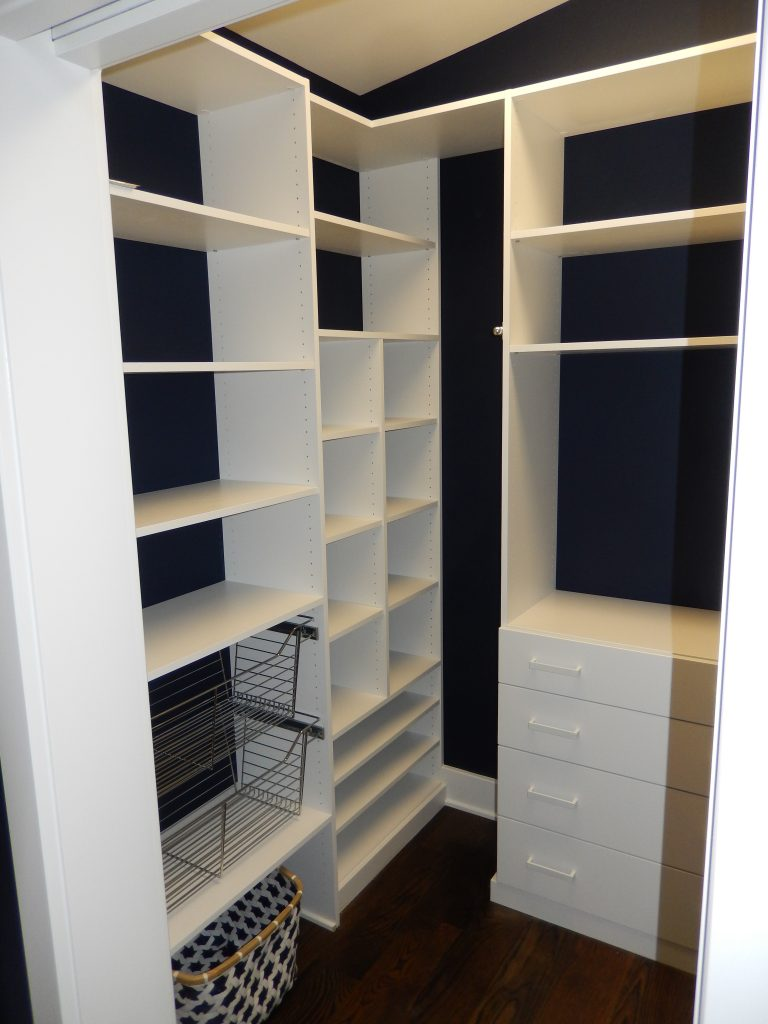 Blue walls and White Shelving over dark wooden flooring. This beautiful walk in closet utilizes its space magnificently.