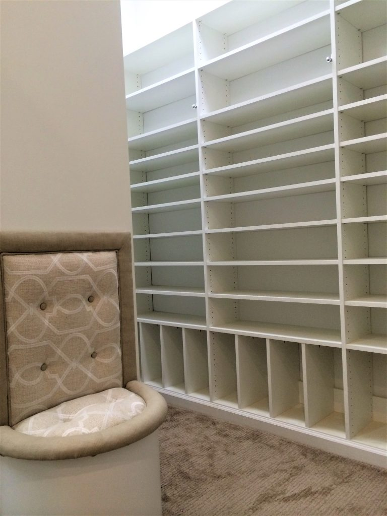 White shelving and muted toned walk-in closet
