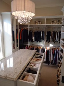 Beautiful white walk-in closet with island drawers and shelving and a chandelier.